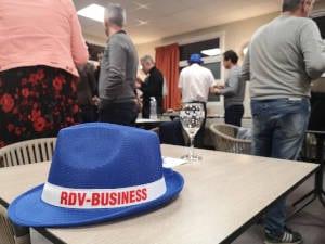 Photo d'une réunion de l'association RDV Business avec, au premier plan, le chapeau du groupe, posé sur une table